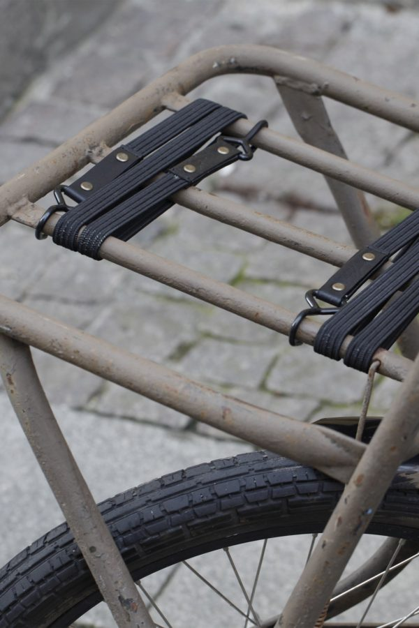 Oaks & Phoenix's bungee straps in black with black leather attached to a bike rack