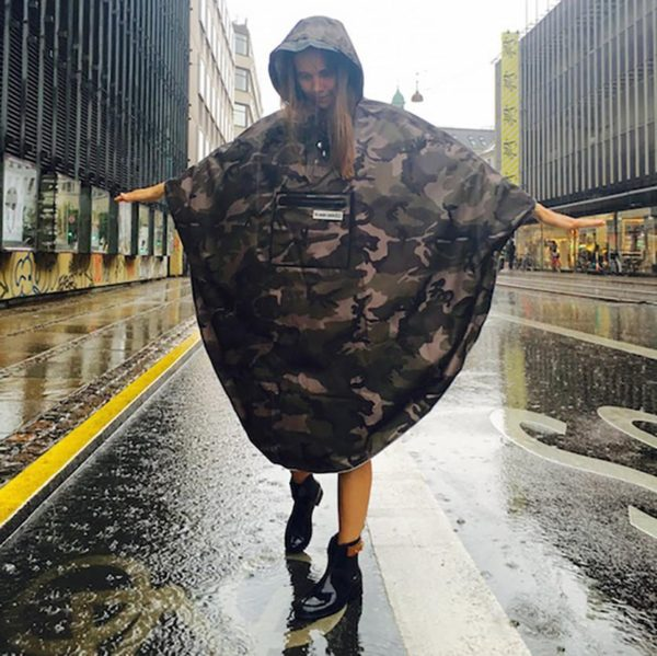 A woman with The people's poncho in camoflage standing in the rain