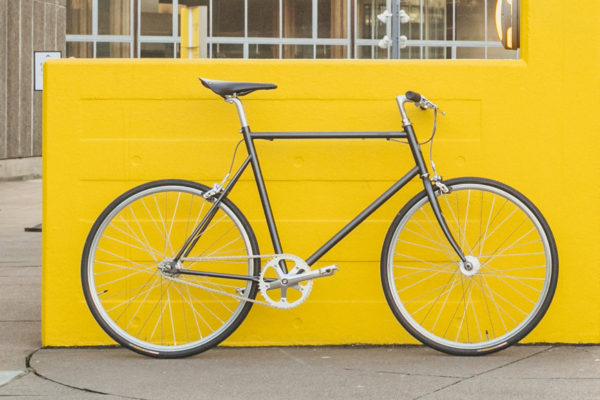 Tokyobike Single Speed standing against a yellow wall