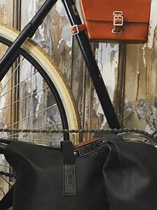 A rear bicycle wheel and two backpacks from Brooks England
